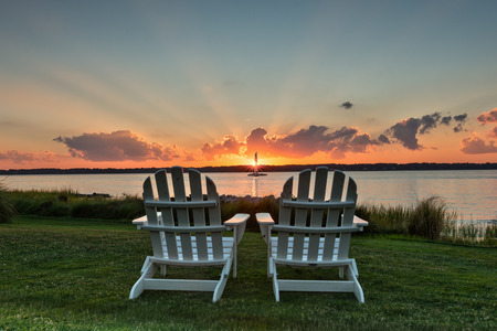 Two chairs facing Hilton Head bay viewing an iconic sunset with rays of light extending beyond the clouds. Reklamní fotografie