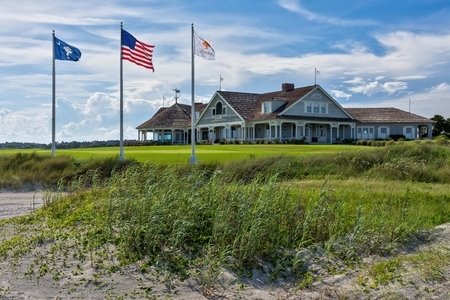 Kiawah Islands famous Ocean Course is iconic to golfers with the sand in the foreground, three flag poles along with the resort in background.