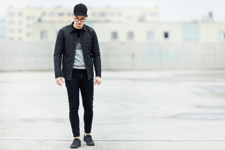 black sweater: Fashionable man walking on the street with blur background Stock Photo