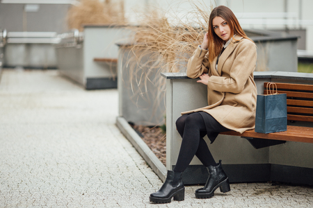 sitting on the ground: Young woman sitting on the bench and smilling to camera