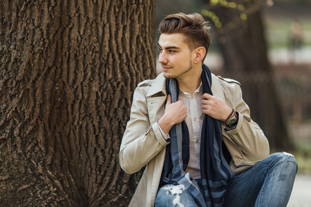 Fashionable man sitting near trees with blur background Stock Photo