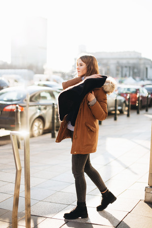 Young pretty girl walk on the street. Hang her scarf in one hand and look around. Winter clothing with warm weather