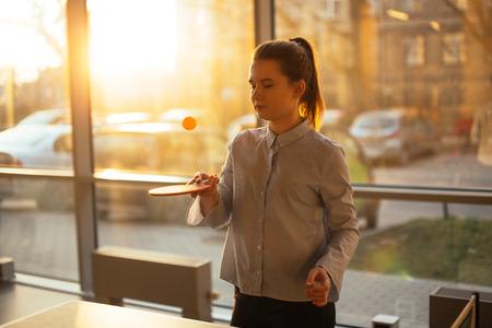 Posto ufficio con ragazza gioca a pin-pong. La ragazza sorridente esamina la macchina fotografica e intorno con la faccia graziosa. Ufficio lavoratore pausa, gioco.