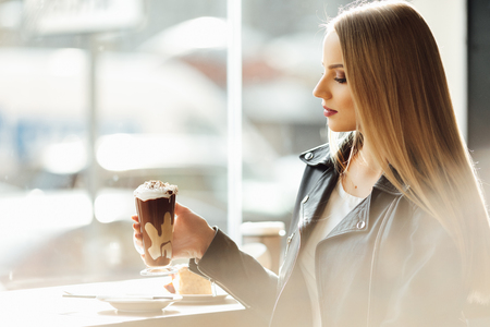 Pretty girl hold a cup of delicious coffee and waer glasses. Sun shine photo with girl drink her cappucino