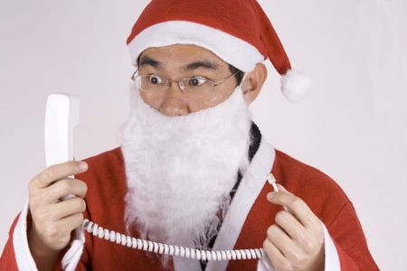 Asian Santa Claus holding a telephone receiver with expression. photo