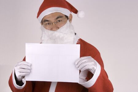 Asian santa claus holding a blank paper. photo