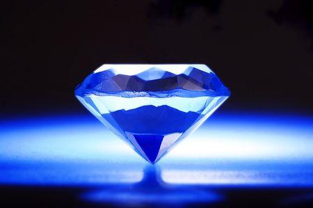 Een diamon in blauwe achtergrond met stralenkrans.