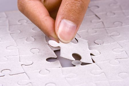 Close up of hand playing jigsaw puzzle.