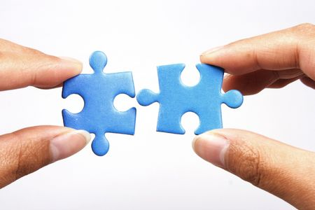 Hands holding two jigsaw puzlle for joining.
