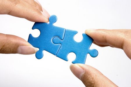 Hands holding two jigsaw puzlle for joining. photo