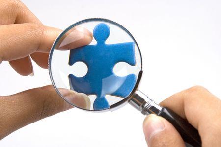 puzzelen: Handen met vergroot glas over een stukje van de puzzel.