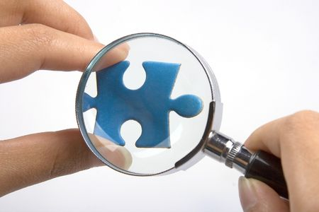 Handen met vergrootglas over een stuk van de puzzel.