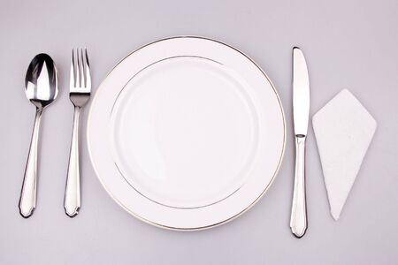 Place setting of a dinning set in white background.