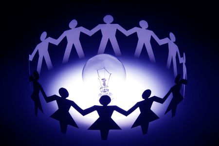 A group of diversify paper chain people surrounding a light bulb.