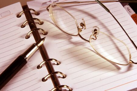 Address book with eyeglasses and fountain pen in warm color. Stock Photo - 677279