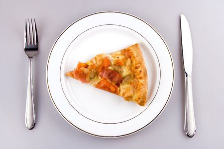 A piece of pizza with place setting.