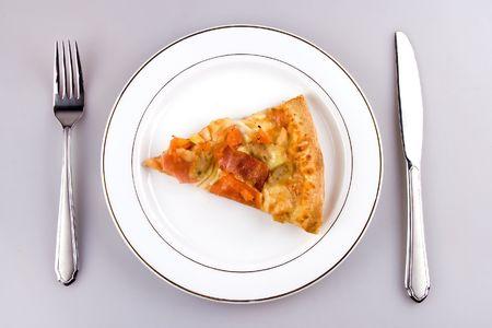 Een stuk pizza met plaats instelling.