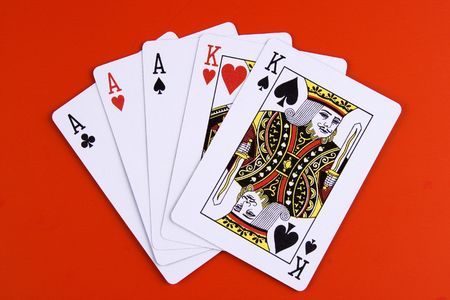 poker game: A full house poker game on red background. Editorial