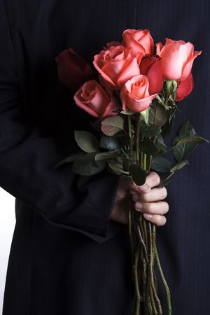 A man with business suite holding roses proposing. Stock Photo