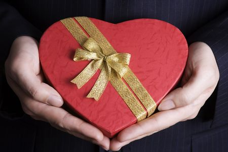 Both hand holding a heart shape gift box. photo