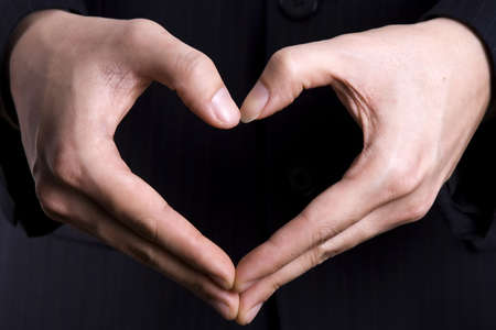 A heart gesture in black isolated background.
