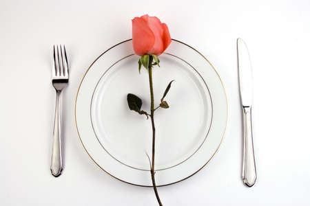 Place setting with pinky rose in white background.