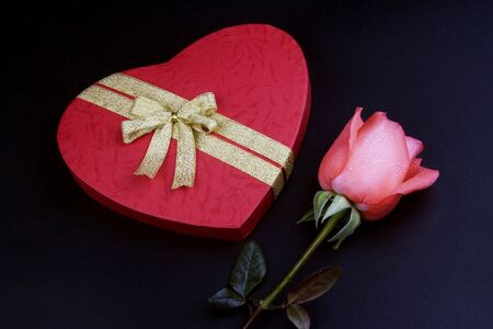 Pink rose with red love shape gift box. photo