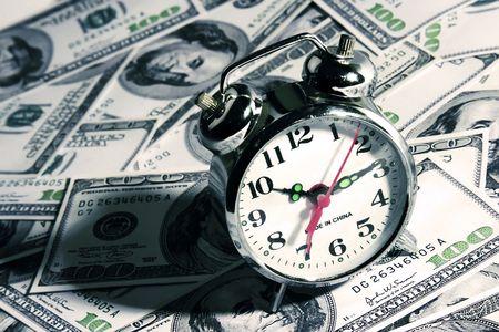 An alarm clock over a hundred dollar bill.