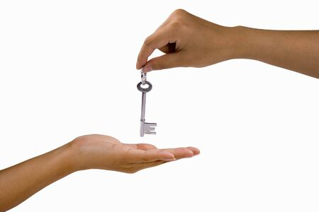 in escrow: Hand over a key in white isolated background.