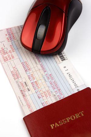 Online boeken vliegticket met computermuis en paspoort.