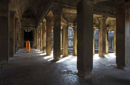 social history: Angkor Wat interior, there is a monk walking on the corridor.