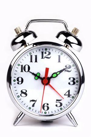 An antique alarm clock in white background. Stock Photo