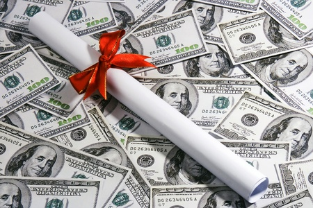 A rolled up certificate lay over hundred dollar notes.
