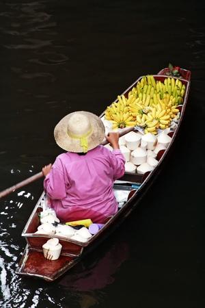 A woman selling fruits at Bangkok floating market. Stock Photo