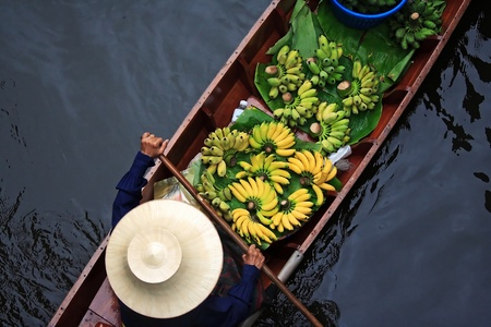 A woman selling fruits at Bangkok floating market. Stock Photo
