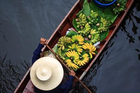 fruit trade: A woman selling fruits at Bangkok floating market. Stock Photo