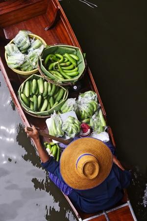 Een vrouw de verkoop van vruchten in Bangkok drijvende markt. Stockfoto