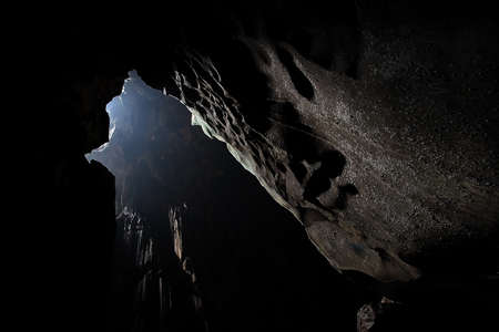 A large cave with sun ray in dark enviroment.