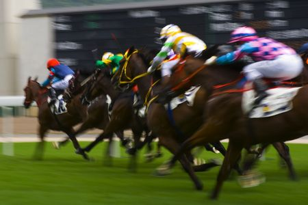 speed race: The Horse Racing at Hong Kong Jockey Club. (got some noise due to high ISO and blurry for motion effect) Stock Photo