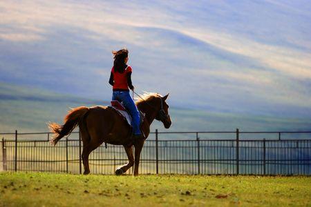 Een Aziatisch meisje rijdt op een paard weer thuis. Stockfoto