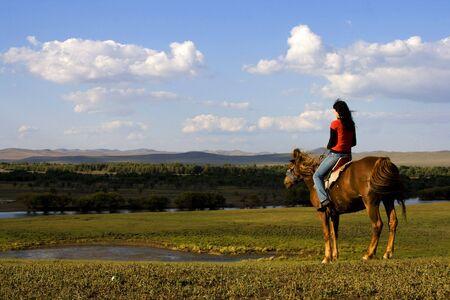 An asian girl horse riding at the grassland. photo