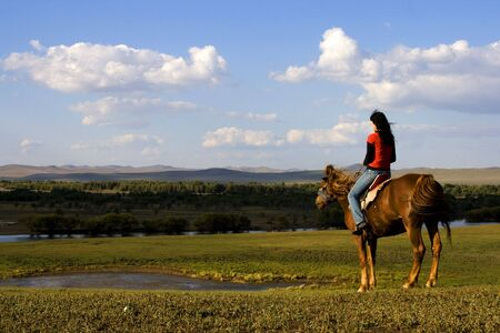 An asian girl horse riding at the grassland. Stock Photo