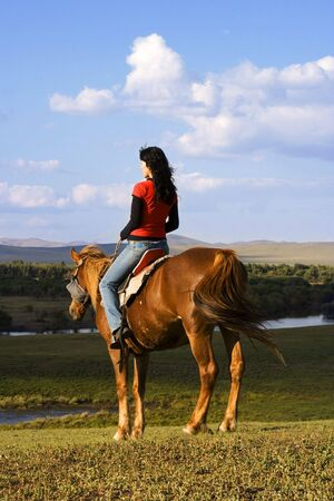 An asian girl horse riding at the grassland. Stock Photo - 2241239