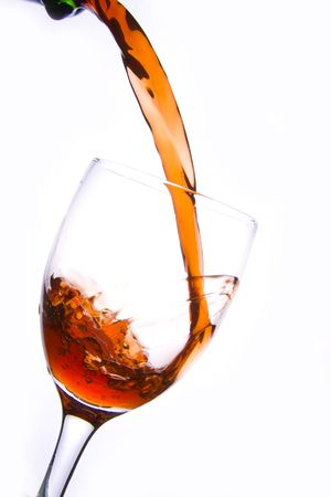 Pouring the red wine into the wineglass in white background.