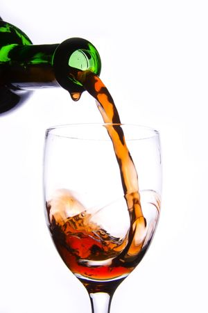 Pouring the red wine into the wineglass in white background. Stock Photo - 2272115