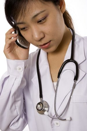 Female doctor with mobile phone in white background. photo