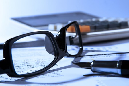 Financial statement with calculator, eyeglasses and fountain pen. Stock Photo