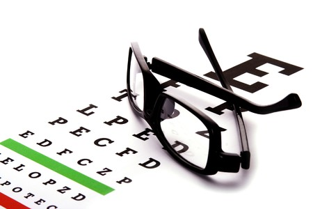 eye red: An eye chart with a black frame eyeglasses.