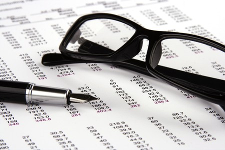 correlate: A Financial statement with eyeglasses and fountain pen.