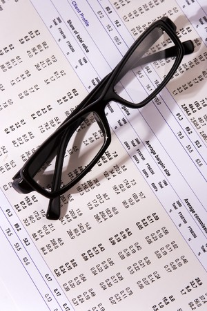 correlate: Eyeglasses on a financial statement with side light. Stock Photo